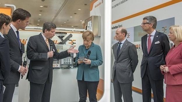 Bundeskanzlerin Angela Merkel ist interessiert und lässt sich die neuen Produkte erklären