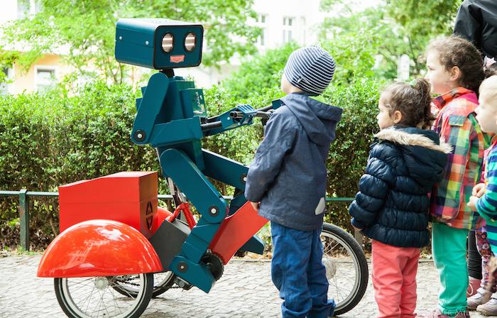 hugo der sprechende Roboter auf rotem Fahrrad mit kindern