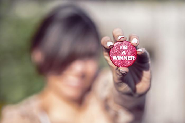 I'm a Winner Frau hält button