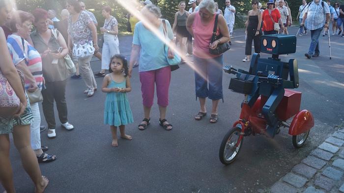 Veträumtes Mächen mit mobilem Künstler auf dem Sommerfest