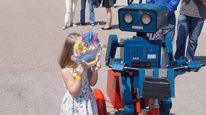 Kleines Mädchen zeigt Hugo ihre selbst gebastelte Roboter Maske