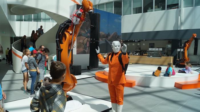 Maschinenmensch vor einem Kuka Industrie Roboterarm