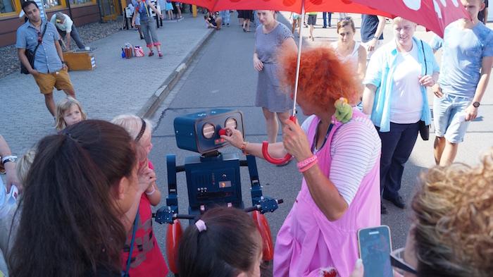 idee-mitarbeiterfest-sprechender-roboter-hugo-auf-fahrrad-clown-rote-nase