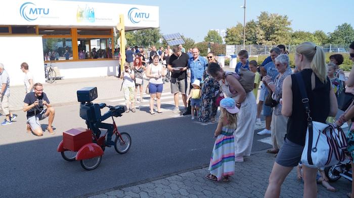 idee-mitarbeiterfest-sprechender-roboter-hugo-auf-fahrrad-eingang-begruessung