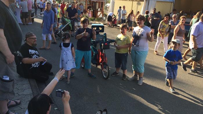 idee-mitarbeiterfest-sprechender-roboter-hugo-auf-fahrrad-daumen-hoch
