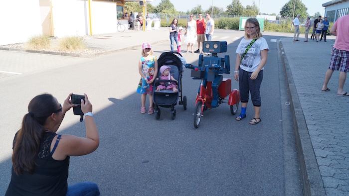 idee-mitarbeiterfest-sprechender-roboter-hugo-auf-fahrrad-familienfoto