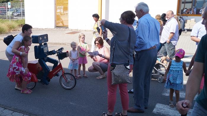idee-mitarbeiterfest-sprechender-roboter-hugo-auf-fahrrad-foto