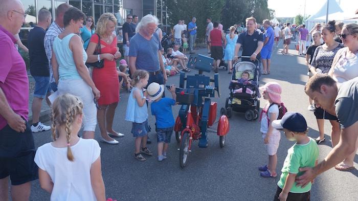 idee-mitarbeiterfest-sprechender-roboter-hugo-auf-fahrrad-guten-tag