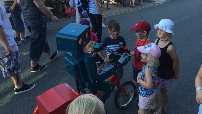 idee-mitarbeiterfest-sprechender-roboter-hugo-auf-fahrrad-habt-ihr-schon-eis-gegessen