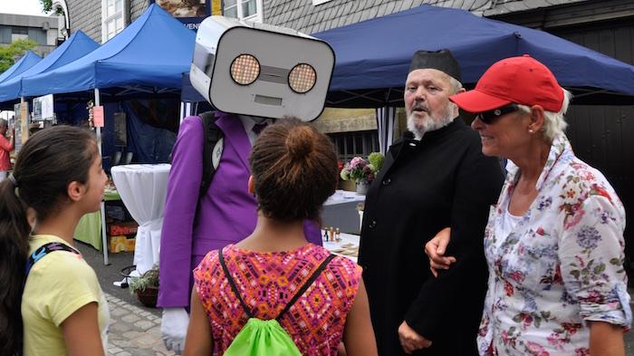 sprechender-roboter-act-steve-machine-in-brilon-pinker-anzug-gespraech-mit-gaesten