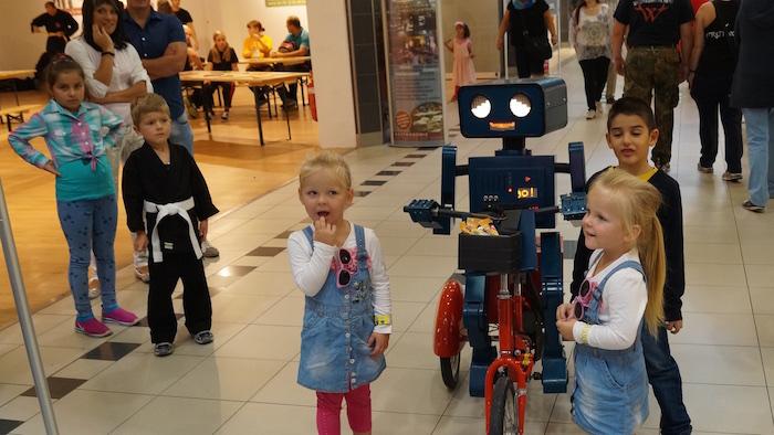 kuenstler-verkaufsoffener-sonntag-vos-hugo-sprechender-roboter-auf-fahrrad-maedchen-blonde-zwillinge