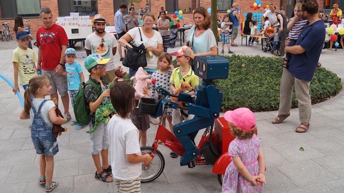 mitarbeiterfest-charite-berlin-hugo-der-sprechende-roboter-mit-fahrrad-kinder-erzaehlen-von-kuscheltieren
