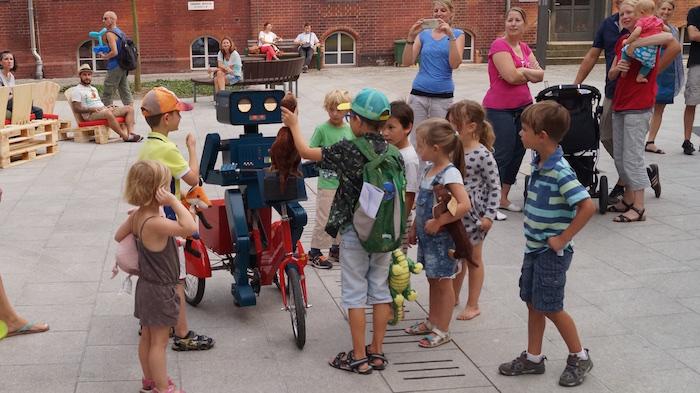 mitarbeiterfest-charite-berlin-hugo-der-sprechende-roboter-mit-fahrrad-kinder-mit-kuscheltieren