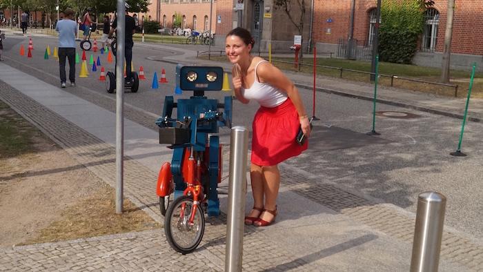 mitarbeiterfest-charite-berlin-hugo-der-sprechende-roboter-mit-fahrrad-junge-frau-roter-rock