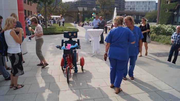 mitarbeiterfest-charite-berlin-hugo-der-sprechende-roboter-mit-fahrrad-krankenschwestern